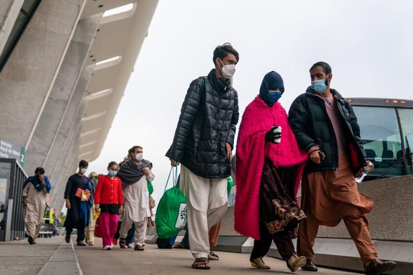 پیاده شدگان از مقابل ساختمان فرودگاه به سمت اتوبوس حرکت می کنند