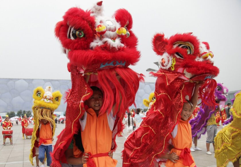Chinese lion dancers rehearse in Beijing on July 30 for a Winter Olympics bid show.