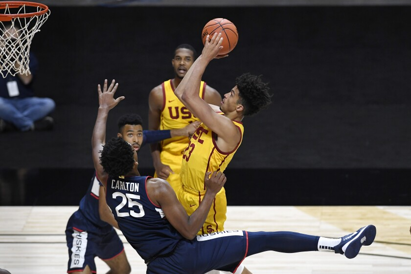 Connecticut's Josh Carlton fouls USC's Max Agbonkpolo during the first half.