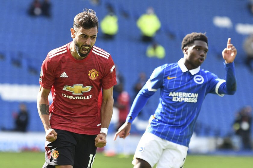Manchester United's Bruno Fernandes celebrates after he scores his sides third goal from the penalty spot during the English Premier League soccer match between Brighton Hove Albion and Manchester United in Brighton, England, Saturday, Sept. 26, 2020. (Glyn Kirk/Pool via AP)