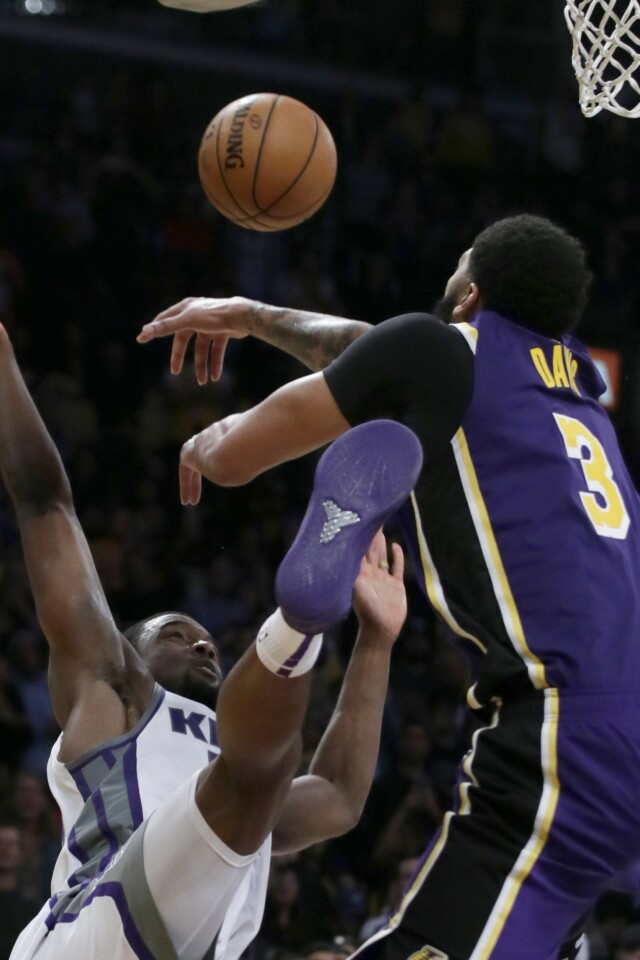 Los Angeles Lakers forward Anthony Davis, right, blocks a shot by Sacramento Kings forward Harrison Barnes, left, in the last second of an NBA basketball game in Los Angeles, Friday, Nov. 15, 2019. The Lakers won 99-97. (AP Photo/Alex Gallardo)