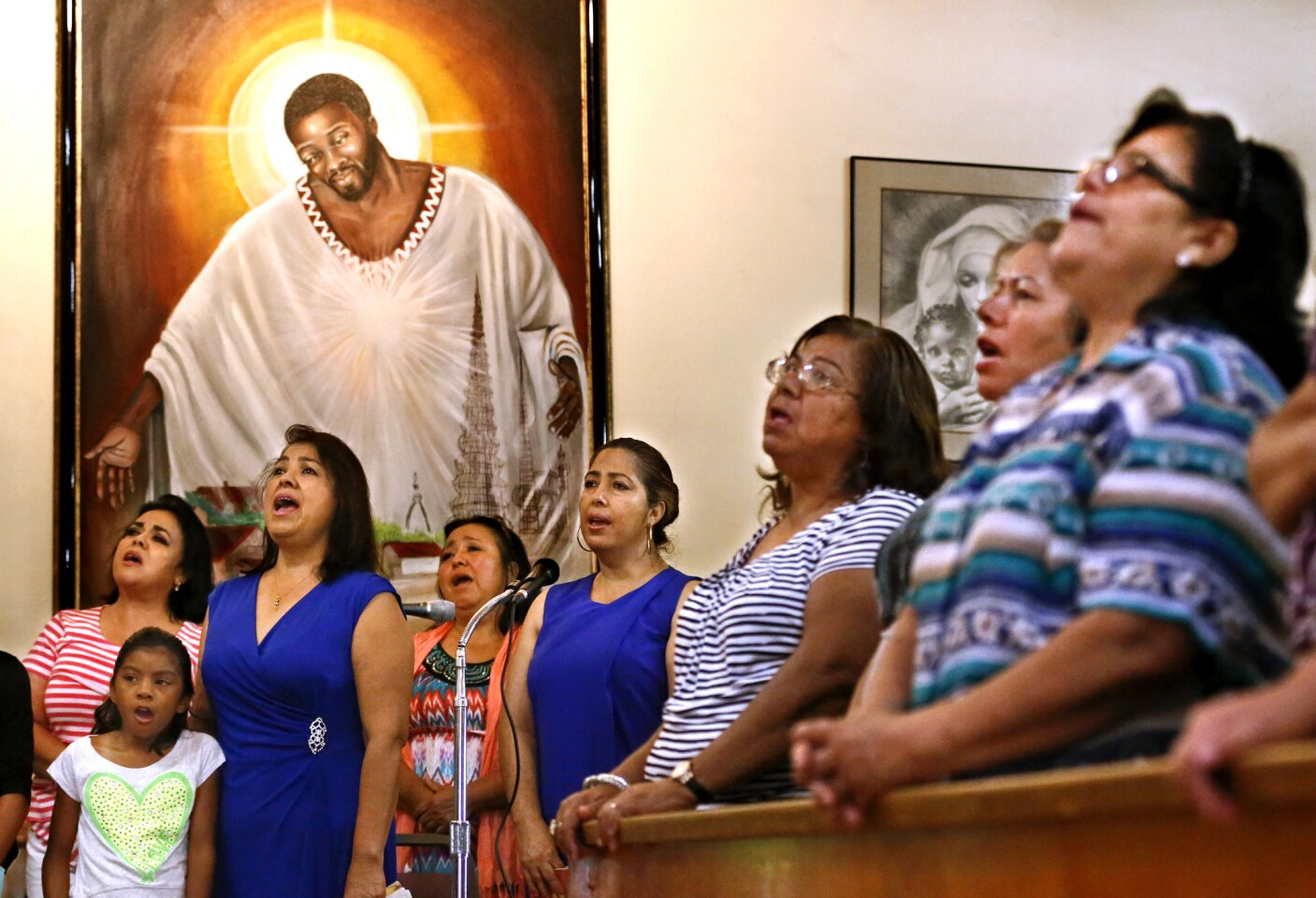 """Members of St. Lawrence Brindisi Church on Compton Avenue in Watts sing during Sunday morning Mass on July 26, 2015. In the background is a painting known as """"Jesus of Watts"""" that was donated to the church some 20 years ago."""