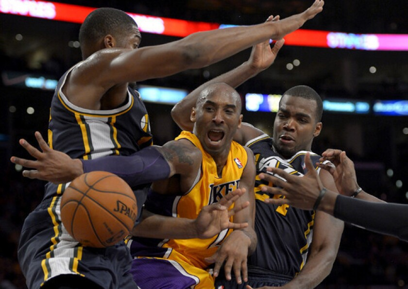 Lakers guard Kobe Bryant makes a pass after driving down the lane against Jazz big men Derrick Favors and Paul Millsap during a game earlier this season at Staples Center.