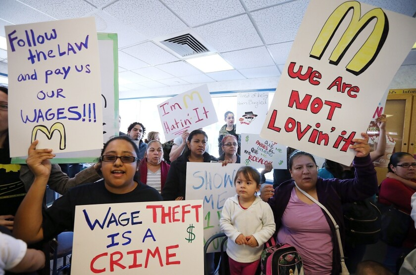 Fast-food workers and activists protest inside a McDonald's restaurant in Oakland.