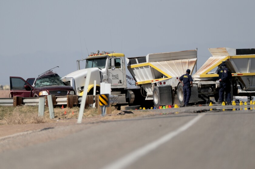 A smashed SUV sits beside a tractor-trailer in Holtville, Calif.