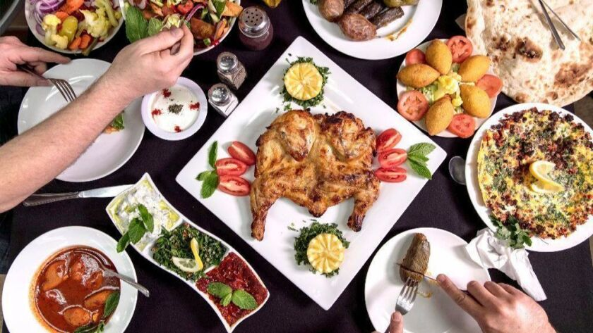 A spread at Akkad Mediterranean & Iraqi Grill that includes tandoori chicken, dips such as jajik (garlicky yogurt) and muhammara (walnut and red-pepper paste with pomegranate sauce), and kebbeh hallab (beef-filled rice croquettes).