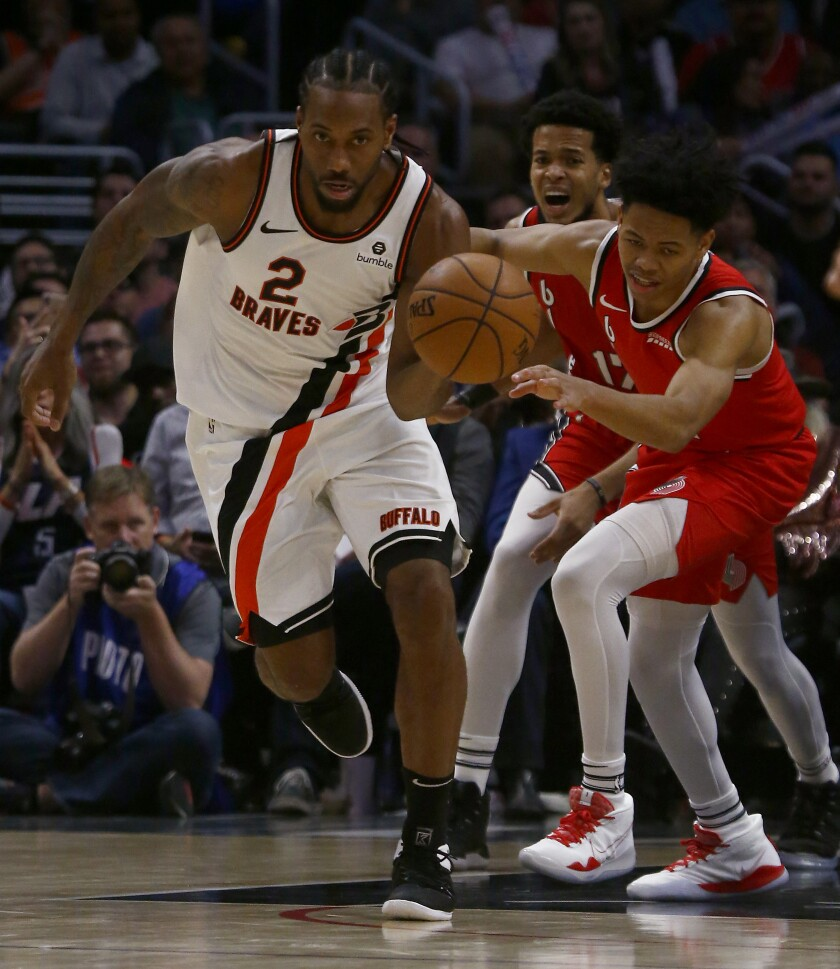 Clippers forward Kawhi Leonard tries to work the ball inside against the Portland Trail Blazers forward Mario Hezonja in the third quarter at Staples Center on Wednesday.