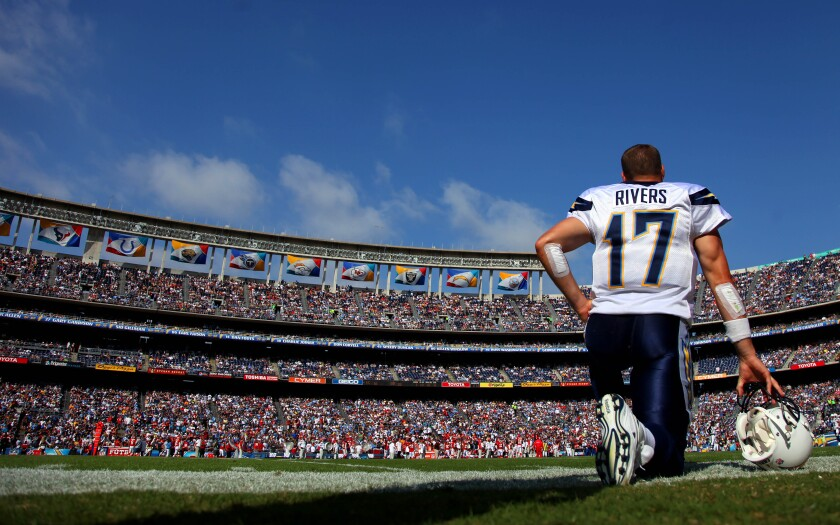 Quarterback Philip Rivers #17 of the San Diego Chargers kneels on the sideline at Qualcomm Stadium.