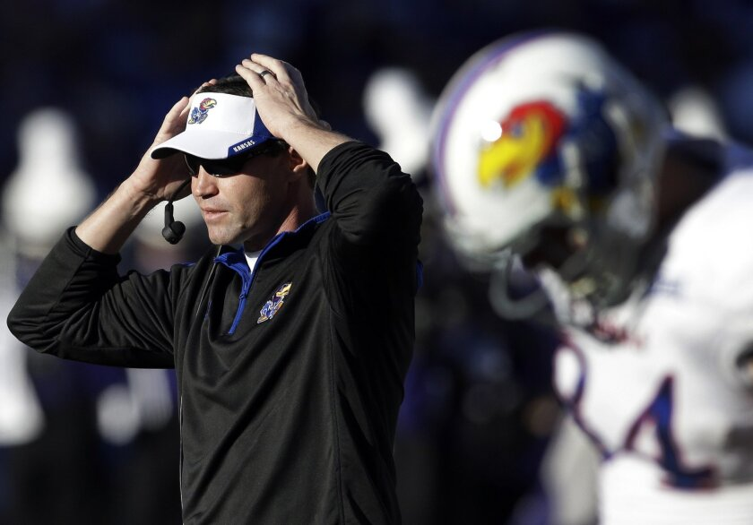 Kansas head coach Clint Bowen adjusts his headset during the first half of an NCAA college football game against Kansas State in Manhattan, Kan., Saturday, Nov. 29, 2014. (AP Photo/Orlin Wagner)