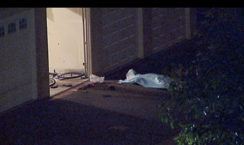A tarp covered a man's body outside a garage at a Vista apartment complex.