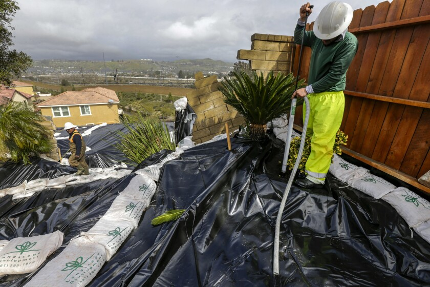 Gonsalo Garcia, right, pumps accumulated rainwater to prevent further erosion on a sliding hillside in Canyon Country on March 2.