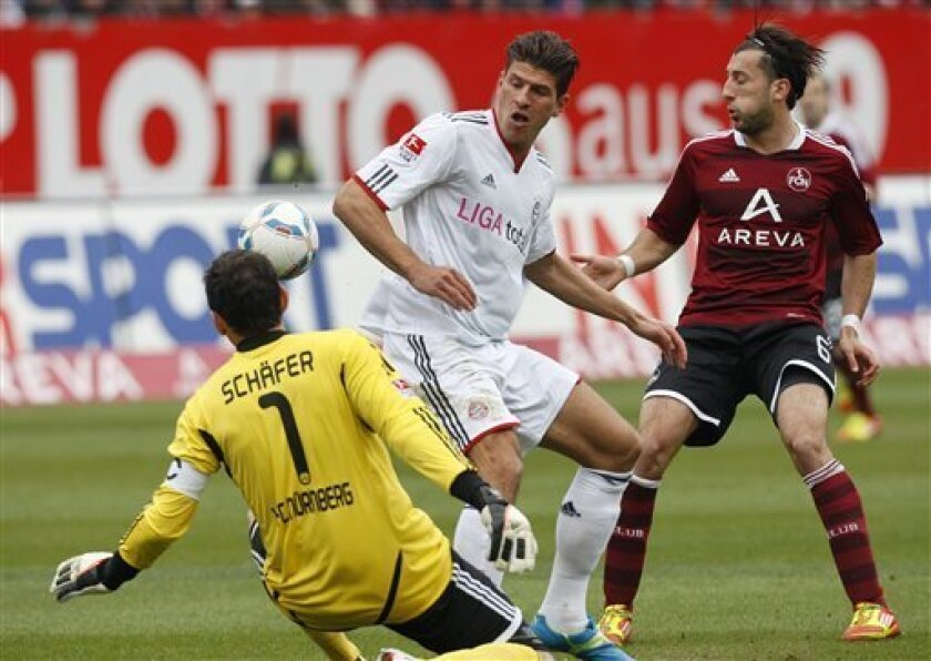 Nuremberg's goal keeper Raphael Schaefer, left, and Dominic Maroh, right, and Munich's Mario Gomez, center, challenge for the ball during the German first division Bundesliga soccer match between 1.FC Nuremberg and Bayern Munich in Nuremberg, Germany, Saturday, March 31, 2012. (AP Photo/Michael Pro
