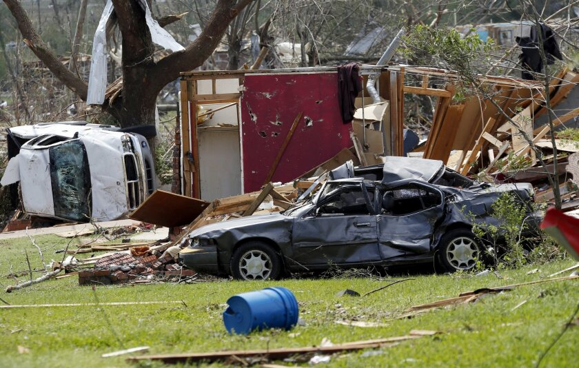 Destroyed automobiles and remnants of homes cover the ground in a south Louisville, Miss., neighborhood, Tuesday, April 29, 2014. A dangerous storm system that spawned a chain of deadly tornadoes over two days flattened homes and businesses, and killed dozens from the Midwest to the Deep South. (AP Photo/Rogelio V. Solis)