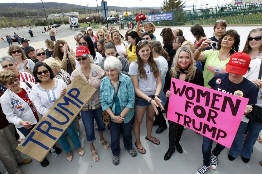 In this photo taken April 25, 2015, a group of women hold signs and shout their support as they wait on line to attend a rally for Republican presidential candidate Donald Trump in Wilkes-Barre, Pa. Trump insists a wide-ranging coalition of Americans will propel him to the White House, yet in the early stages of his general election campaign the presumptive Republican nominee appears to be having trouble even rebuilding even the losing coalition that Mitt Romney managed four years ago, with the skepticism of college-educated whites offering a particularly ominous warning for Trump. (AP Photo/Mel Evans)