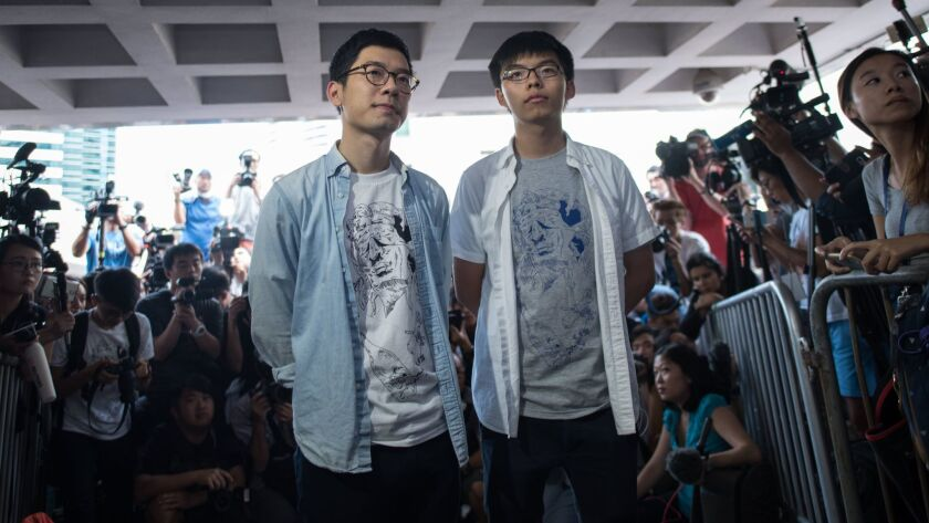Student pro-democracy activists Nathan Law, left, and Joshua Wong speak to the media outside Hong Kong's High Court on Aug. 17, 2017, on the day of their sentencing for unlawful assembly.