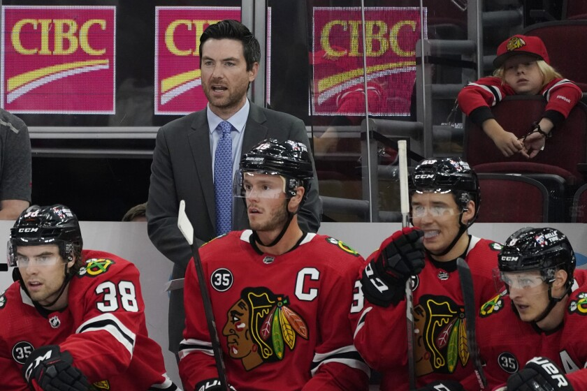 Chicago Blackhawks head coach Jeremy Colliton, top, talks to his team during the first period of an NHL preseason hockey game against the Detroit Red Wings in Chicago, Wednesday, Sept. 29, 2021. (AP Photo/Nam Y. Huh)