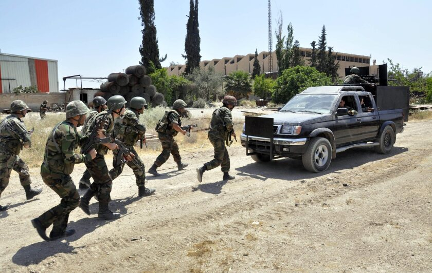 An image made available by the official Syrian Arab News Agency shows government soldiers taking up position during a May patrol in Duma, a suburb of Damascus.