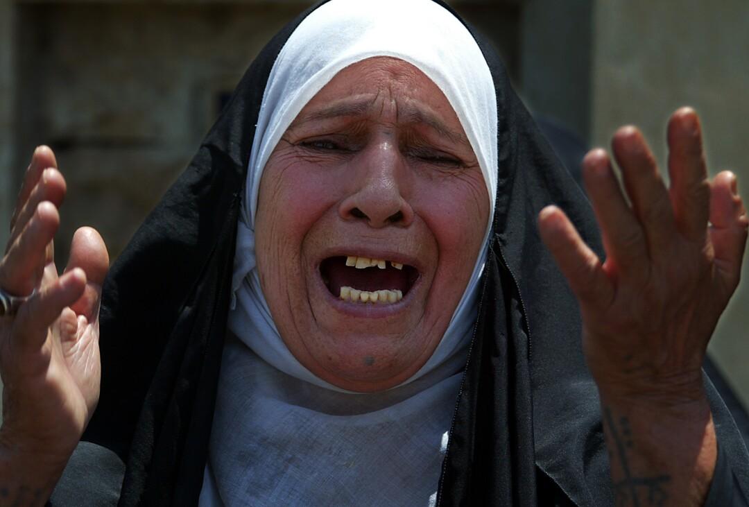 زن باحجاب دستان خود را بالا می آورد و گریه می کند