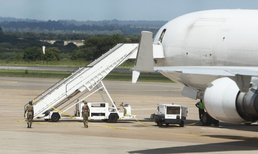 Zimbabwean Armed Soldiers patrol around a United States registered cargo plane at Harare International Airport in Harare, Zimbabwe, Monday, Feb,15.2016. Zimbabwean aviation authorities impounded a U.S.-registered cargo jet after a dead body later believed to be a stowaway and millions of South Afri
