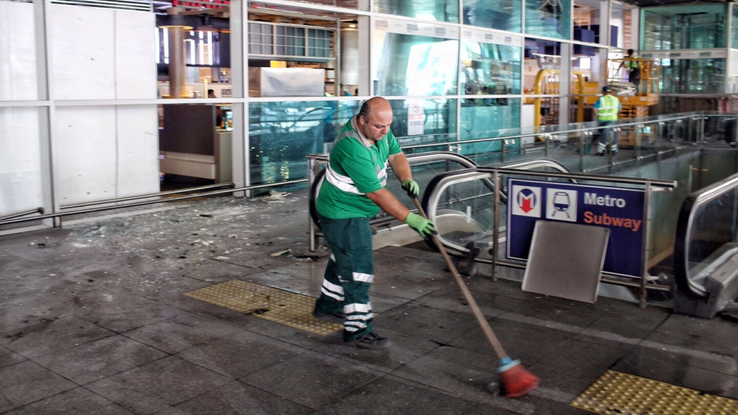 Workers clean the debris from Tuesday's attack at Turkey's largest airport on Wednesday.