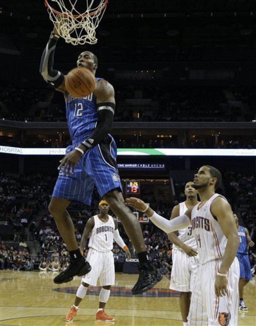 Orlando Magic's Dwight Howard (12) dunks as Charlotte Bobcats' D.J. Augustin (14) and Stephen Jackson (1) look on in the first half of an NBA basketball game in Charlotte, N.C., Saturday, Nov. 6, 2010. (AP Photo/Chuck Burton)