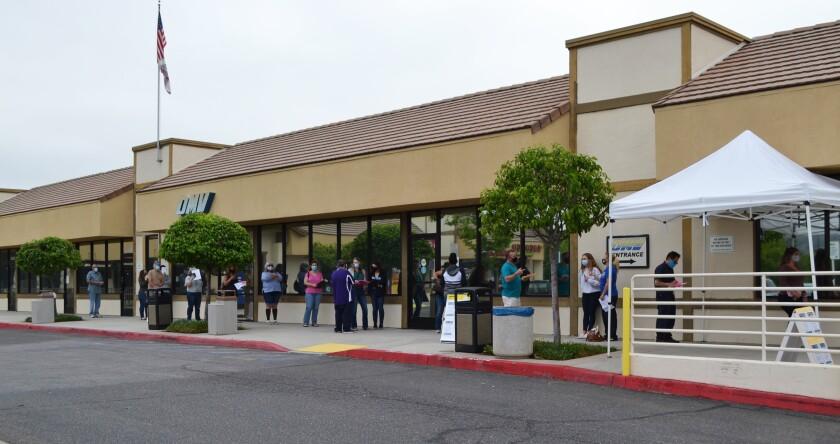 People wait outside the Poway DMV office.