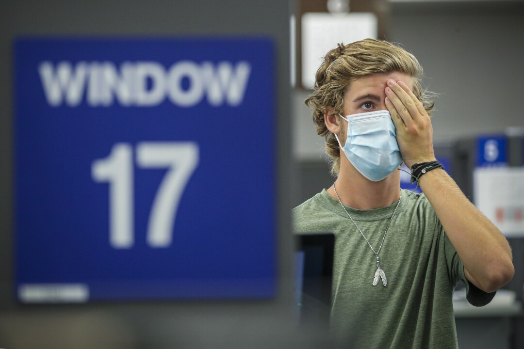 A teenager wearing a mask covers one eye with his hand while applying for his learner's permit at a DMV field office