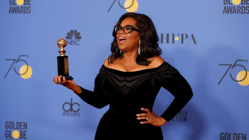 Oprah Winfrey holds her Cecil B. DeMille Award at the Beverly Hilton Hotel on Sunday.