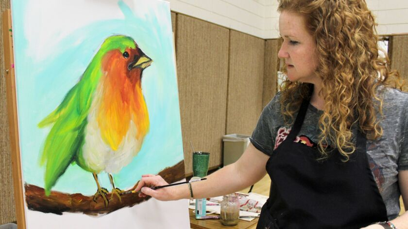Artist Suzi Reil paints a bird for La Crescenta members of the Church of Jesus Christ of Latter-day