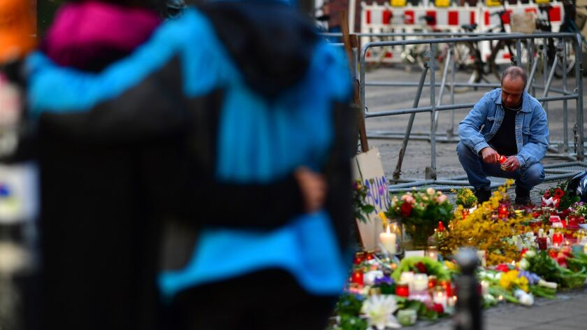 People leave flowers and candles at the scene in Muenster, Germany, where a van was driven into a crowd of people Saturday, leaving two dead and dozens injured.