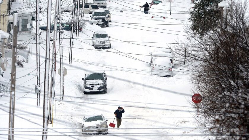 Erie, Pa., residents on East 24th Street dig out on Tuesday, Dec. 26, 2017, after a record two-day s