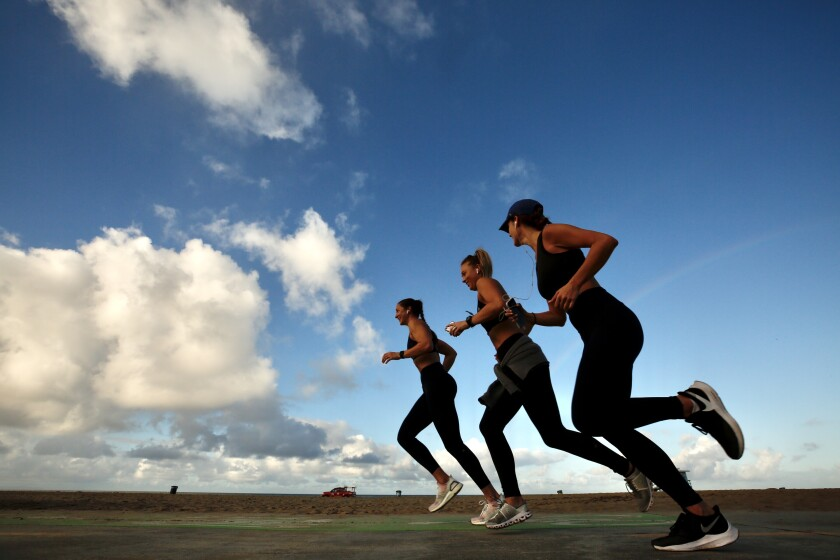 From left; Alysia Vickis, Casey Atamniuk and Courtney Olson, go for their daily morning run at Venice Beach on Monday, after a rain storm blew through the area.
