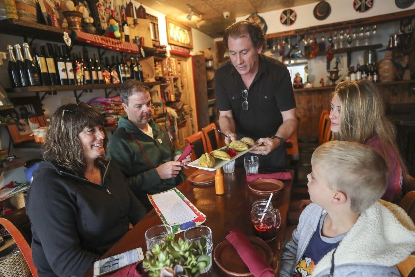 Food server Patrick McBride serves lunch to Darrin and Michelle Hotaling with their children Ethan, 5, and Jessica, 16, at Q'ero on Wednesday, Nov. 27 in Encinitas.