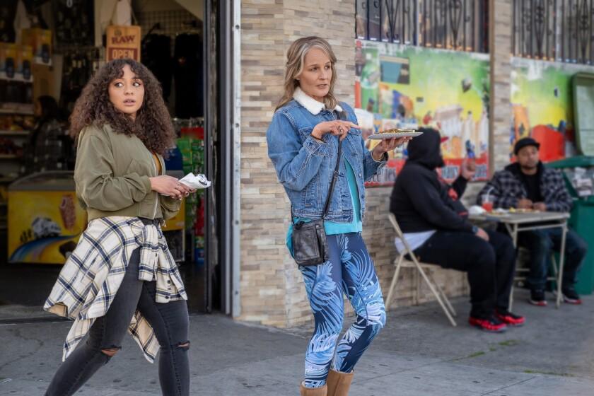 Two women talking on the sidewalk outside an Oakland eatery