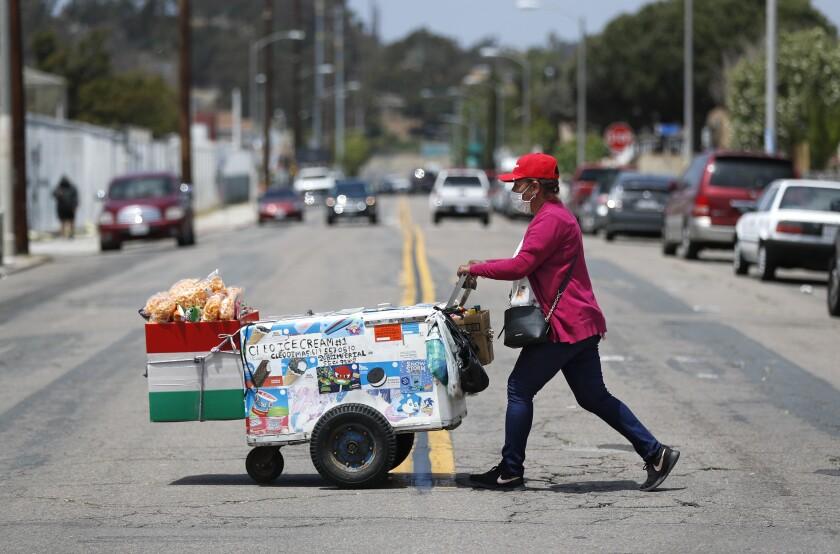 La vendedora Cleotilde Dimas empuja su carrito mientras camina por una calle de Logan Heights