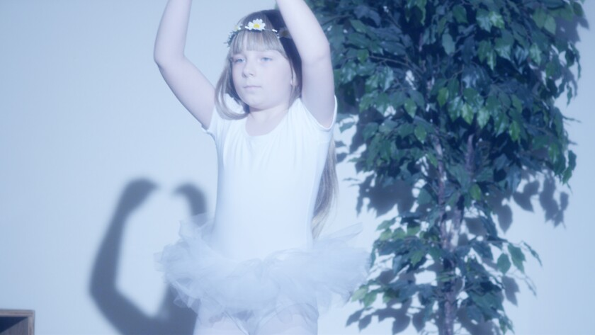 "Colter Carlbom-Mann, a young boy in a tutu with his arms up as if in a pirouette, in the movie ""Ballet Blanc."""