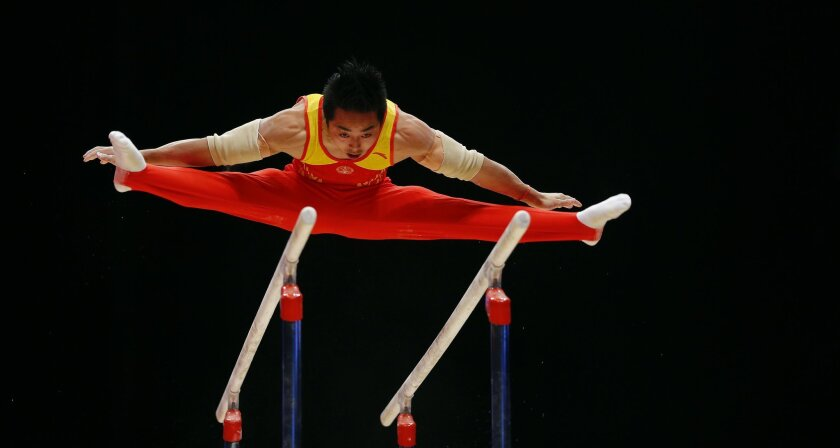 China's Hao You performs on the parallel bars during the men's apparatus final competition at the World Artistic Gymnastics championships at the SSE Hydro Arena in Glasgow, Scotland, Sunday, Nov. 1, 2015. (AP Photo/Matthias Schrader)