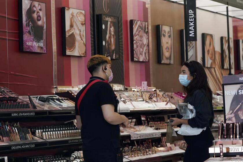 Un trabajador, a la izquierda, atiende a una clienta en una tienda de cosméticos
