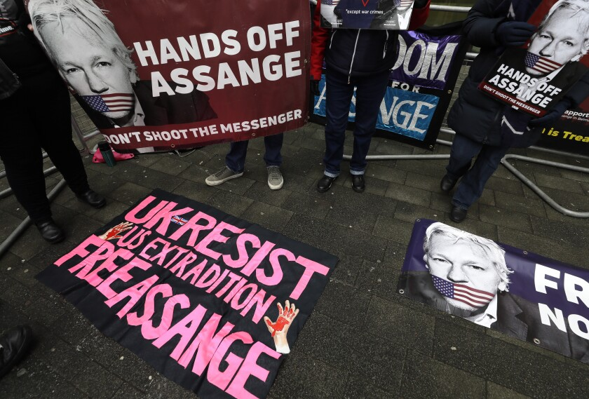 """People hold posters reading """"Hands Off Assange - Don't Shoot the Messenger"""" and """"Free Assange."""""""