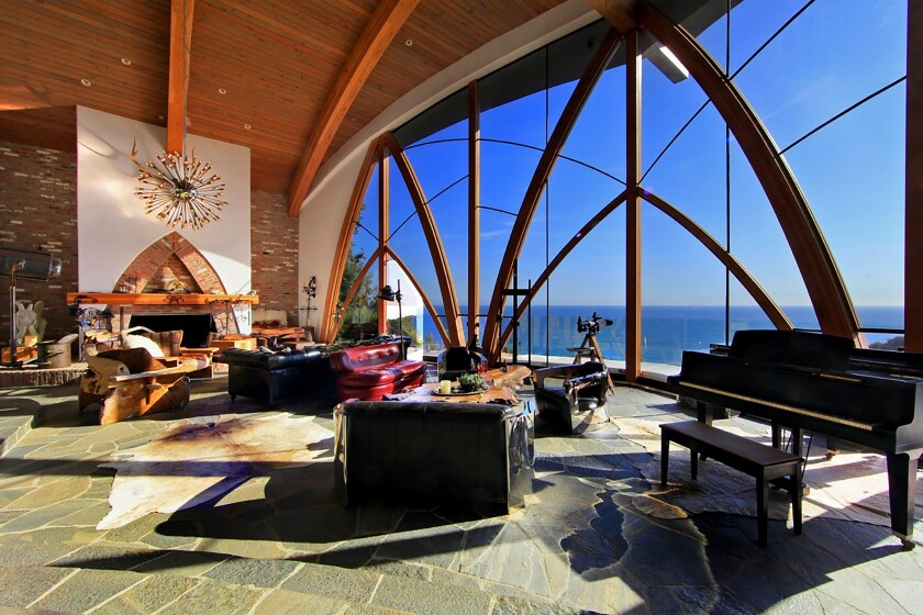 Our Home of the Week in Malibu, designed by architect Harry Gesner, features expanses of glass, Gothic arches, stone floors.