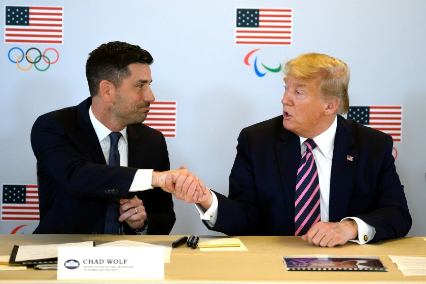 President Trump shakes hands with acting Homeland Security Secretary Chad Wolf during a briefing with the U.S. Olympic and Paralympic Committee and LA 2028 Olympic organizers in Beverly Hills on Tuesday.