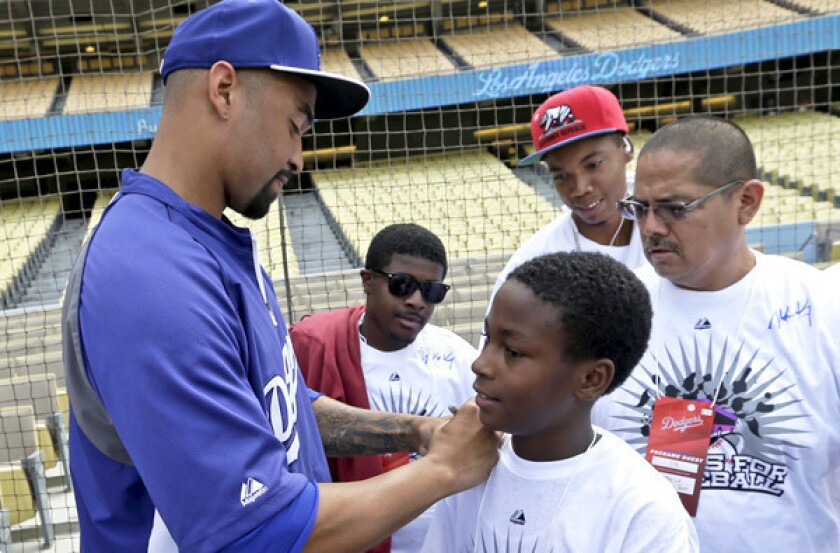 Dodgers center fielder Matt Kemp autographs a fan's shirt before a game against the Cincinnati Reds last month.