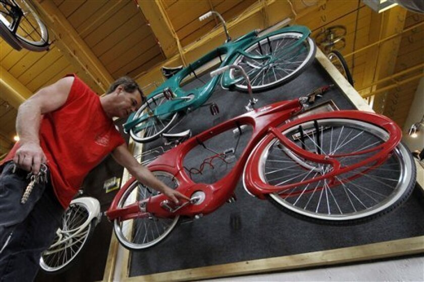 In this June 29, 2011 photo, Craig Morrow, 54, of Ben Avon, Pa., talks about a display of Bowden Spacelanders, the first bicycles with fiberglass frames, in his new bike shop and museum, Bicycle Heaven, in Pittsburgh. Bicycle Heaven is a repository for Morrow's collection of 1,500 bicycles and some 90,000 parts and accessories. (AP Photo/Gene J. Puskar)