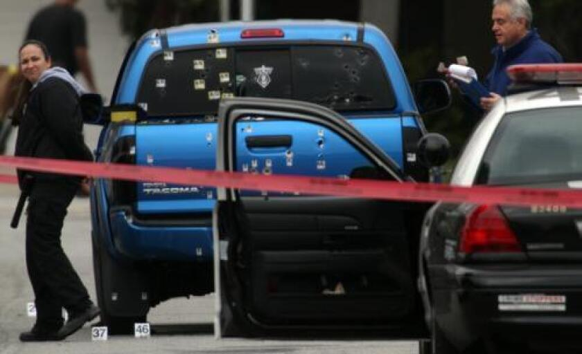 Police investigators work around a blue pickup truck riddled with bullets in the 19500 block of Redbeam Avenue in Torrance after a police protection team fired on it.