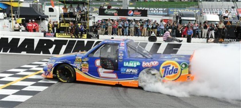 Kevin Harvick does a burnout in his Tide truck after winning the NASCAR Truck Series auto race on Saturday, March 31, 2012, in Martinsville, Va. (AP Photo/Don Petersen)