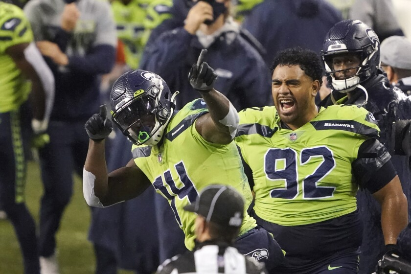 Seattle Seahawks' Bryan Mone (92) cheers on DK Metcalf (14) after Metcalf pulled in a long pass near the end of the second half of an NFL football game against the Minnesota Vikings, Sunday, Oct. 11, 2020, in Seattle. The Seahawks won 27-26. (AP Photo/Ted S. Warren)