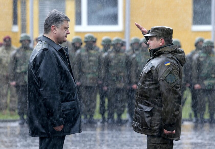 A Ukrainian soldier salutes President Petro Poroshenko during the rain-drenched opening ceremony for Operation Fearless Guardian, a U.S. training mission for Ukrainian national guard troops.