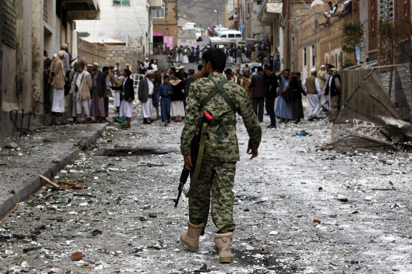 An armed member of the Houthi militia walks through the scene of a car bomb attack targeting a mosque in Sana, Yemen, on July 29.