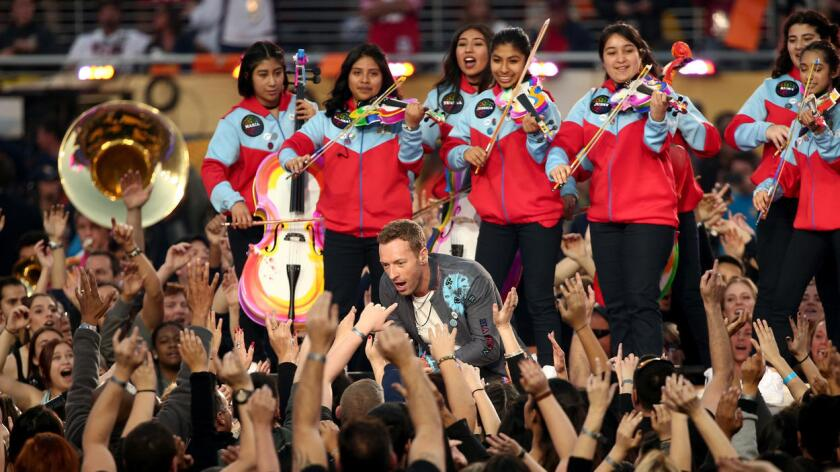 """Con un cartel en la mano en honor a su hijo, el violinista Marc, Ofelia, expresó que """"quería llorar"""" cuando le vio actuando y aseguró que fue """"una experiencia inolvidable, quizá única en la vida"""". En la foto los estudiantes de YOLA con el vocalista de Coldplay."""