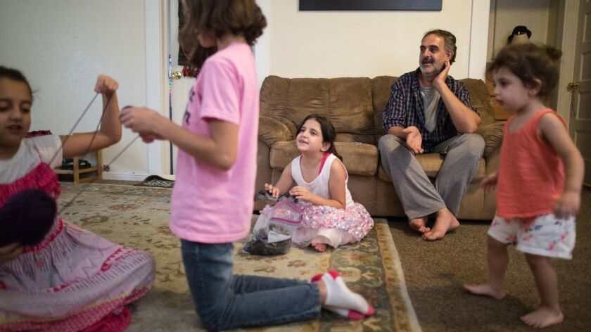 Syrian refugee Taiseer Al Souki, right, relaxes at home with his family in Fresno.